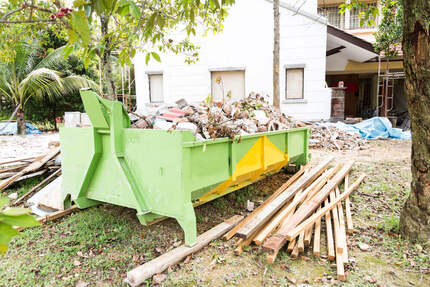 image of a residential skip hire bin out the front of a house being demolished surrounded by timber planks