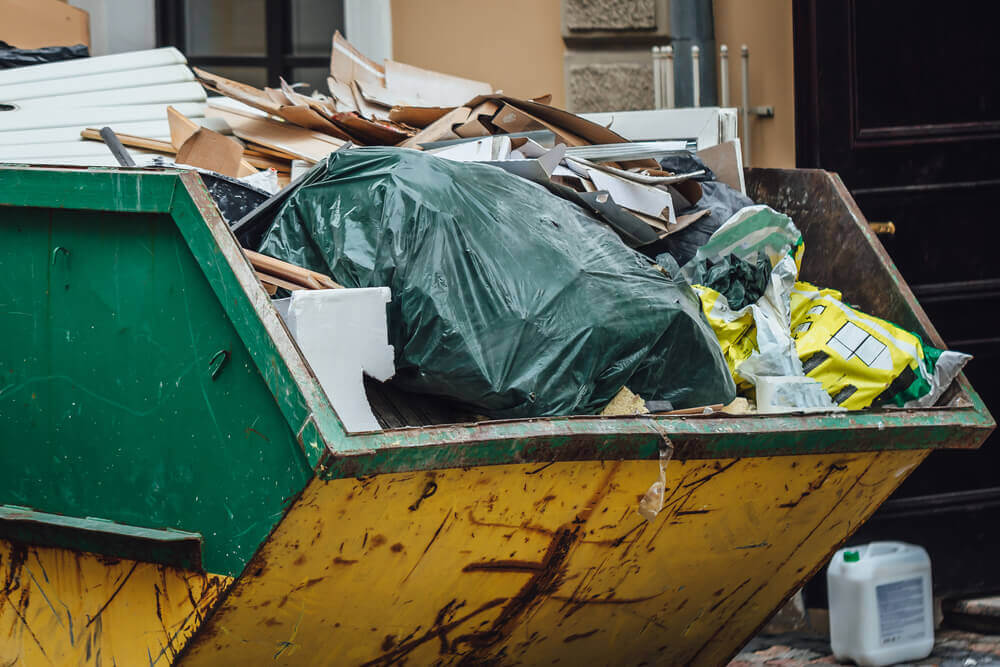 close up view of a yellow and green residential skip hire bin filled with household rubbish