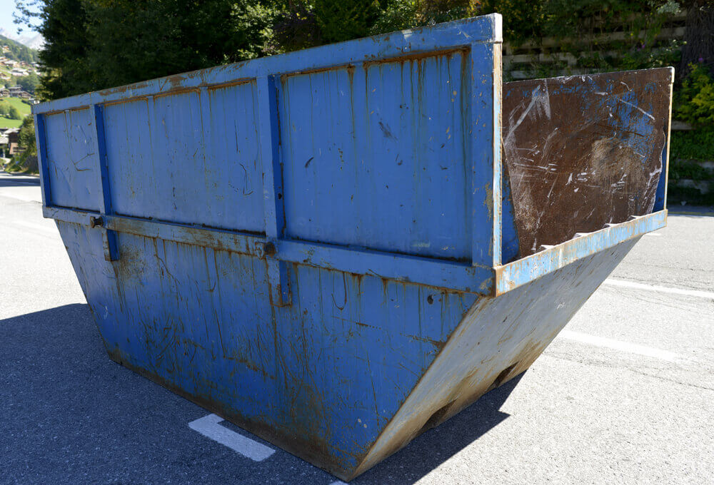 image of a blue residential skip hire bin with high sides sitting in the middle of a road